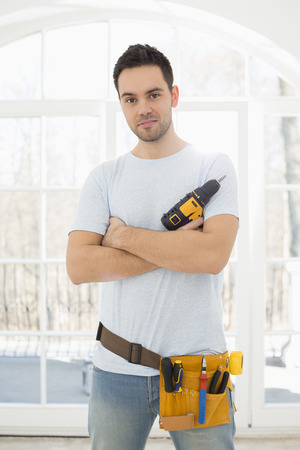hand drill: Portrait of confident man with hand drill in new house