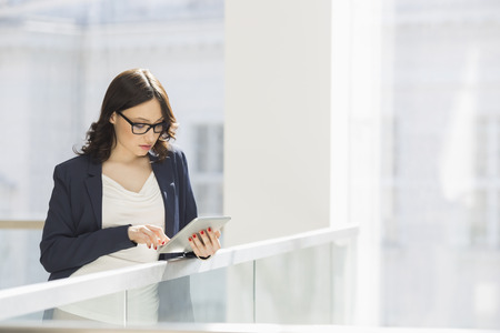 business attire: Young businesswoman using tablet PC in office
