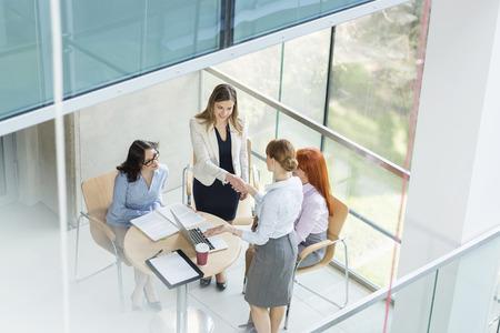 Hohe Winkel der Unternehmerinnen Händeschütteln am Tisch im Amt LANG_EVOIMAGES