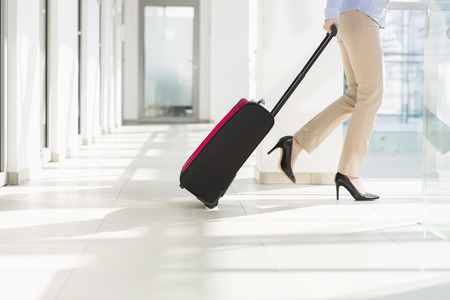 low section: Low section of businesswoman with luggage exiting airport LANG_EVOIMAGES