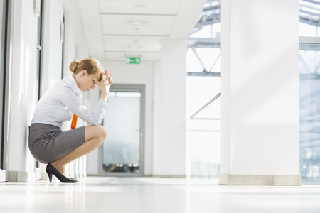 worried woman: Full-length side view of stressed businesswoman crouching at office hallway