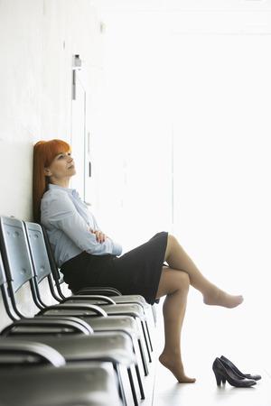 Durchdachte Geschäftsfrau sitzt mit gekreuzten Beinen auf dem Stuhl im Amt