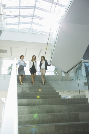 moving down: Happy businesswomen conversing while moving down steps in office