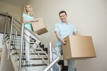 moving down: Couple carrying cardboard boxes while moving down steps at new home LANG_EVOIMAGES