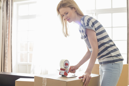 moving box: Woman packing moving box at home LANG_EVOIMAGES
