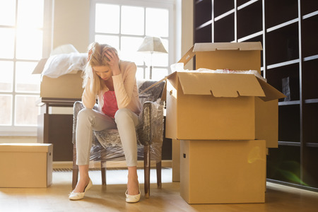 moving in: Full-length of frustrated woman sitting by cardboard boxes in new house LANG_EVOIMAGES