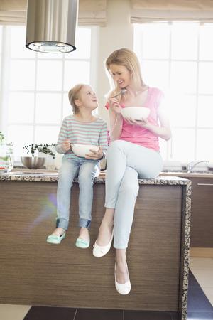 madre soltera: Madre e hija mirando el uno al otro mientras toma el desayuno en la cocina