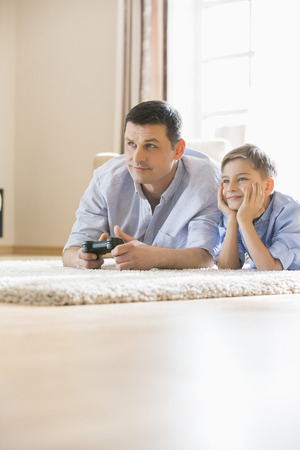 playing video game: Father and son playing video game on floor at home