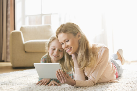 parents with one child: Mother and daughter using digital tablet on floor at home
