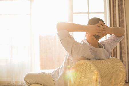 estilo de vida: Opinião traseira do homem que relaxa na cadeira em casa