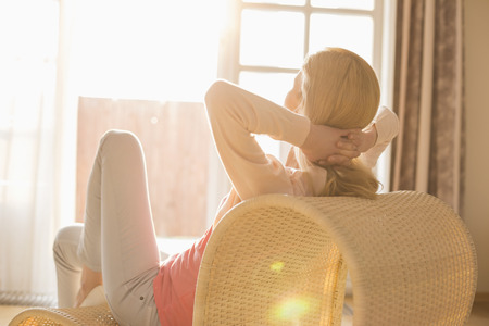 Rear view of woman relaxing on chair at home 写真素材