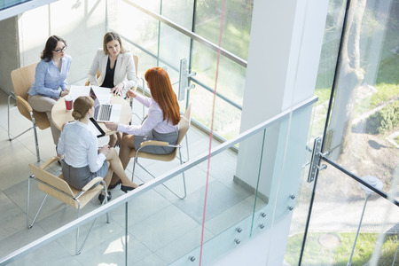 office attire: High angle view of businesswomen discussing at table in office LANG_EVOIMAGES