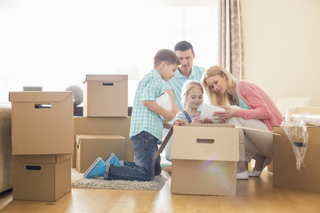 family moving house: Family unpacking cardboard boxes at new home