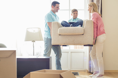 family moving house: Parents carrying son on armchair in new house