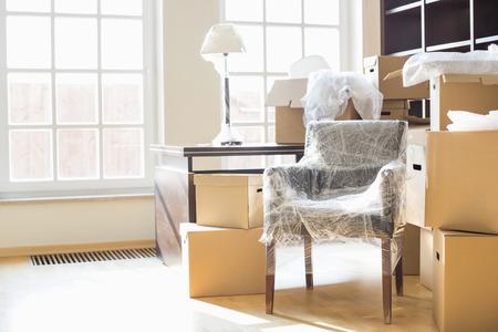 Verhuisdozen en meubels in een nieuw huis Stockfoto