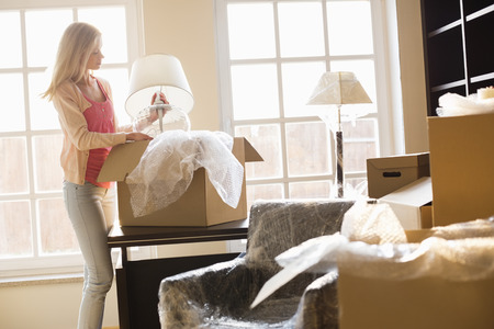 moving in: Woman removing lamp from moving box at new house