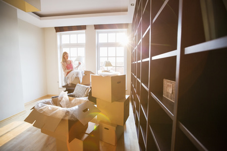 moving box: Woman unpacking lamp from moving box at new house