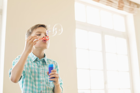 elementary age boys: Boy blowing bubbles at home LANG_EVOIMAGES