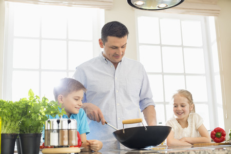 father daughter: Children looking at father preparing food in kitchen