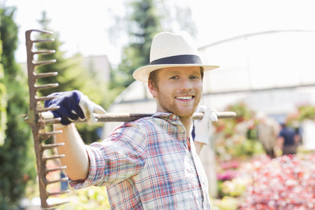 incidental people: Portrait of smiling gardener carrying rake on shoulders at plant nursery