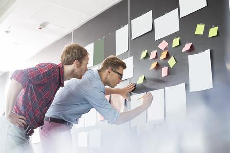 Ondernemers analyseren documenten op de muur in het kantoor