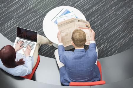 personas leyendo: Vista de �ngulo alto de la lectura de peri�dicos hombre de negocios, mientras que su colega femenina usando la computadora port�til en la oficina