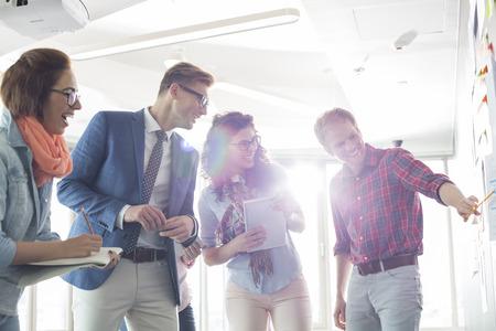 Smiling Geschäftsmann zu erklären, Kollegen im Büro kreative