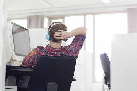 person sitting: Vista posterior del joven empresario llevando auriculares en escritorio de la computadora en la oficina LANG_EVOIMAGES