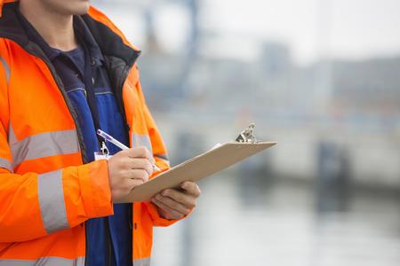 empleados trabajando: Secci�n media de hombre de mediana edad escrito en el portapapeles en el patio del env�o