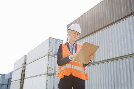 cargo container: Female worker reading clipboard in shipping yard