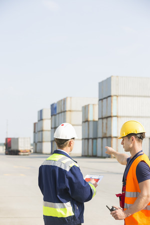 side job: Rear view of male workers discussing in shipping yard LANG_EVOIMAGES