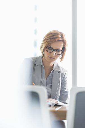cabello corto: La empresaria joven escribiendo en el escritorio en la oficina
