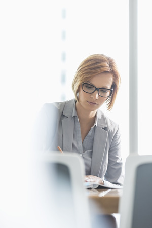 short hair: Young businesswoman writing at desk in office