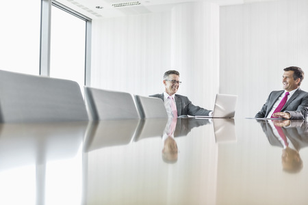 conference room table: Smiling businessmen talking in conference room
