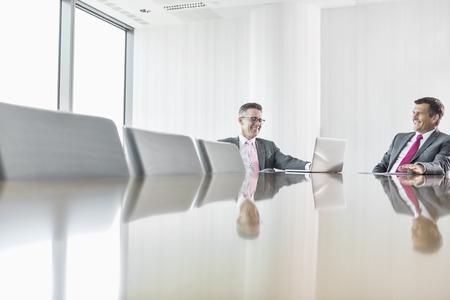 dos personas hablando: Sonriendo empresarios hablando en la sala de conferencias