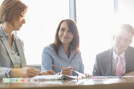 conference room table: Smiling businesswoman with colleagues in meeting room
