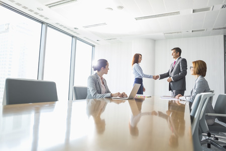 business connections: Businessman and businesswoman shaking hands in conference room