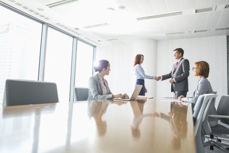 handshake: Hombre de negocios y empresaria agitando las manos en la sala de conferencias