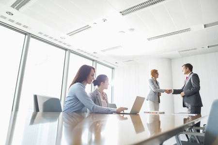 Businesspeople shaking hands in board room
