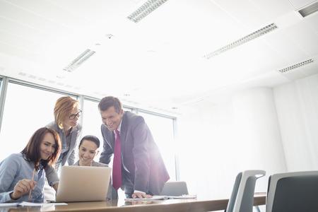 会議用テーブルでノート パソコンを使用しての実業家