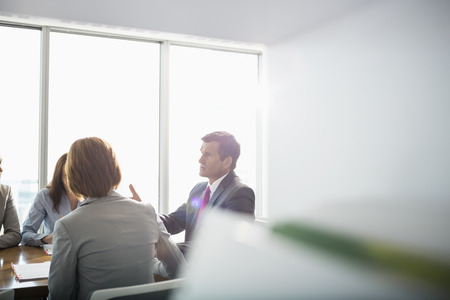 Businessman discussing with female team in conference room LANG_EVOIMAGES