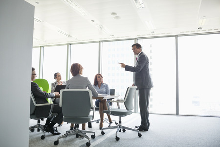 conference room table: Businessman giving presentation in conference room LANG_EVOIMAGES