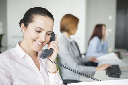 telephone: Smiling young businesswoman using landline telephone with colleagues in background at office