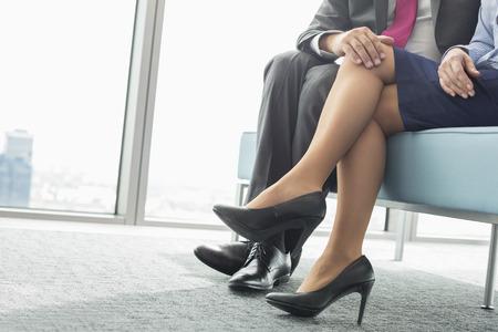 Niedrige Abschnitt der Geschäftsmann flirtet mit weiblichen Kollegen im Büro