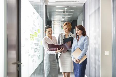women talking: Businesswomen with file folders discussing in office corridor