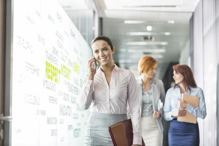 personas mirando: Joven empresaria en llamada con los colegas en fondo en el corredor de la oficina