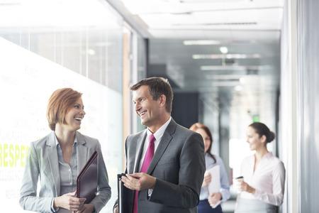 business wear: Business people walking in corridor