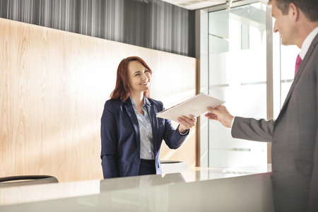 reception desk: Businessman receiving document from receptionist in office