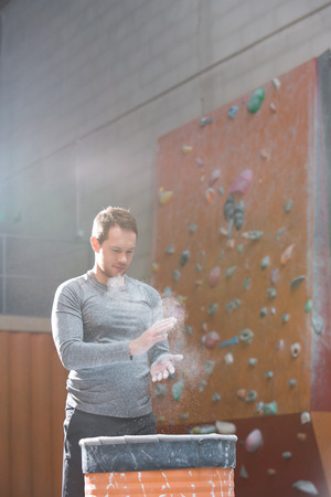 dusting: Low angle view of confident man dusting powder by climbing wall in crossfit gym LANG_EVOIMAGES