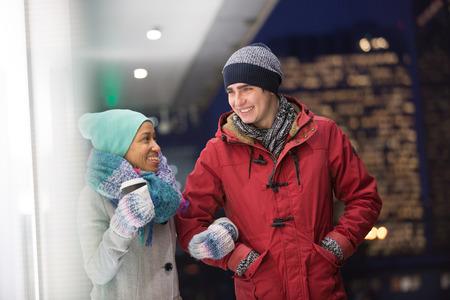 conversing: Multiethnic couple conversing at dusk during winter